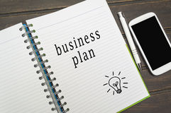 Business plan word in notebook Stock Images