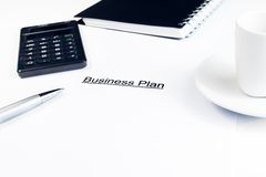 Business plan words near calculator, pen and cup of coffee, business concept Stock Images