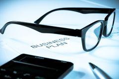 Business plan words near glasses, pen and calculator, business concept Stock Photography