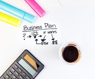 Business plan words near highlighters, calculator and cup of coffee, business concept Royalty Free Stock Image