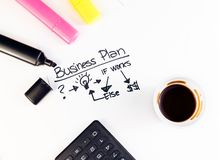 Business plan words near highlighters, calculator and cup of coffee, business concept Stock Photos