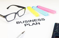 Business plan words near highlighters, calculator and glasses, business concept Stock Images