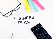 Business plan words near highlighters, calculator and glasses, business concept Royalty Free Stock Photos