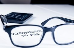 Business plan words see through glasses lens near calculator, business concept Royalty Free Stock Image