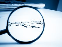 Business plan words see through lens of loupe in front of business newspaper on office table Royalty Free Stock Photo