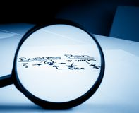 Business plan words see through lens of loupe on office table Stock Photography