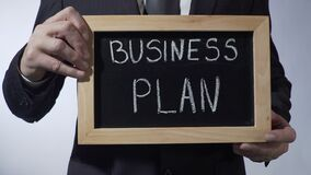 Business plan written on blackboard, male hands holding sign, strategy, goals. Stock footage stock video footage