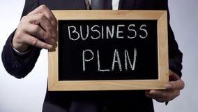 Business plan written on blackboard, male hands holding sign, strategy, goals Stock Photo