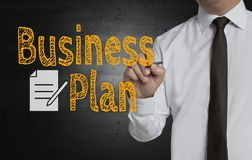 Business plan is written by businessman on screen royalty free stock photos