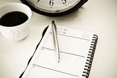 Business planner. With cup of coffee and clock in the background Royalty Free Stock Photography