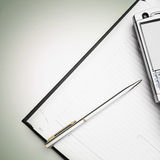 Business planner with a pen and a phone Stock Photography