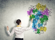 Business planning. Back view of businesswoman drawing business ideas on wall Stock Photos