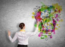Business planning. Back view of businesswoman drawing business ideas on wall Stock Photography