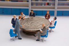 Business Planning Concept. Group of miniatures sitting around a 50 cent piece Stock Photos