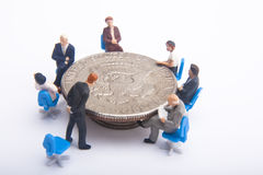 Business Planning Concept. Group of miniatures sitting around a 50 cent piece Stock Images