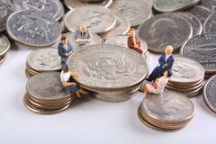 Business Planning Concept. Group of miniatures sitting around a 50 cent piece Stock Photo