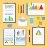 Business planning table with project charts and graphs. Business planning table with office supplies. Open spiral notebook with marketing strategy data, project Stock Photos