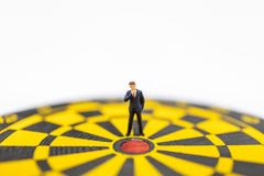 Business, Planning, Target and Goal Concept. Close up of businessman miniature figure standing close to center of  dart board with. White background and copy stock photos