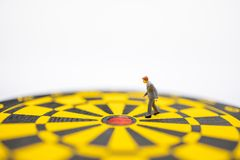 Business, Planning, Target and Goal Concept. Close up of businessman miniature figure walking to center of  dart board with white. Background and copy sapce royalty free stock image