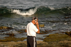 Business and pleasure. Man with headphones and phone on the beach Royalty Free Stock Photos