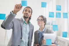 Business points. Two intercultural colleagues lookikng at one of notepapers on transparent board while working in office Stock Image