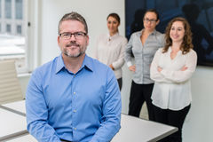 Business portrait of man with three women in the background. Business portrait of men with three women standing in the background royalty free stock photo