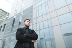 Business portrait of a young man in a suit from the lower angle against the backdrop of modern architecture. A beautiful man with a beard poses against the Stock Images