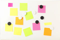 Business 'Post It' notes on magnetic board. Pink,yellow, green'Post It' notes on white magnetic board Stock Photos