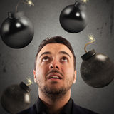 Business preoccupation. Man with worried expression with bombs falling Royalty Free Stock Photography