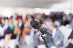 Business presentation. Corporate conference. Microphone. Microphone in focus against blurred audience. Participants at the business or professional conference royalty free stock photo