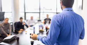 Business presentation on corporate meeting. Business man making a presentation at office. Business executive delivering a presentation to his colleagues during royalty free stock photography