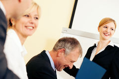 Business presentation in meeting. Business team receiving a presentation held by a female co-worker standing in front of a flipchart Stock Image