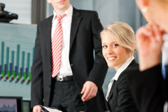 Business - presentation within a team. A female, colleague is standing on the flipchart royalty free stock images