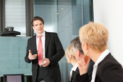 Business - presentation within a team. A male, colleague is standing on the screen Stock Images