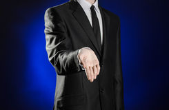 Business and the presentation of the theme: man in a black suit showing hand gestures on a dark blue background in studio isolated Royalty Free Stock Image
