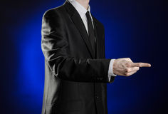 Business and the presentation of the theme: man in a black suit showing hand gestures on a dark blue background in studio isolated Royalty Free Stock Photo