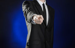 Business and the presentation of the theme: man in a black suit showing hand gestures on a dark blue background in studio isolated Stock Image