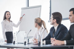 Business presentation. Business women speaking at presentation and pointing to white board stock photography
