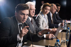 Business press conference. Young businessman giving press conference with microphone stock photo