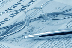 Business press, glasses and pen (blue toned) Royalty Free Stock Photography
