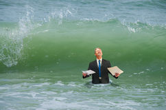 Business pressure man getting hit by wave Stock Photo