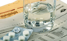 Business Problem. Aspirin, glass with water on business newspaper Stock Photo