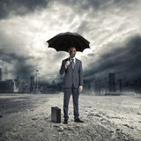 Business problem. A businessman wearing a gas mask, standing in the rain Stock Images
