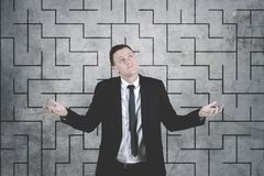 Confused businessman against complicated maze drawing background. Business problem concept: Confused businessman against complicated maze drawing background Stock Photos