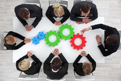 Business problem solution concept. Business problem solution, mechanism of business, teamwork concept, business team sitting around white table with cogs Stock Photos