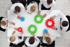 Business problem solution concept. Business problem solution, mechanism of business, teamwork concept, business team sitting around white table with cogs Stock Images