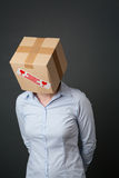 Business Problems and Worries. Businesswoman with box labeled fragile over her head looks down in sadness before a dark background Royalty Free Stock Photography