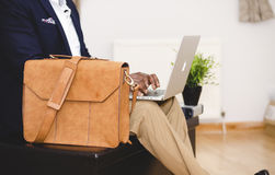Business professional with briefcase and laptop. Business professional seated with leather briefcase and open laptop inside Royalty Free Stock Images