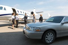 Business Professional Greeting Airhostess And. Pilot near private jet and limo Royalty Free Stock Photography