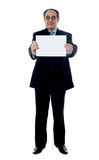 Business professional holding blank billboard. Senior business professional showing blank clipboard to camera isolated on white Royalty Free Stock Images